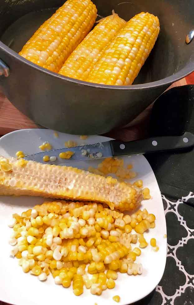corn on a white plate cut off the cob and a pot full of corn on the cob in the background