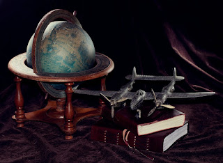 Model of a Lockheed p-38 with an antique globe and leather journals