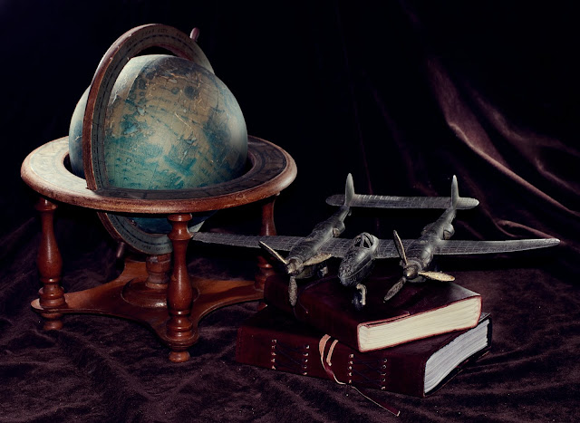 still life of a vintage globe and airplane with leather-bound journals
