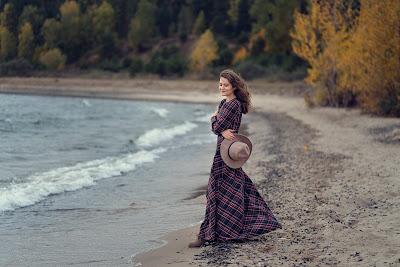 Chica con vestido largo y sombrero en la orilla de la playa con bosque de fondo