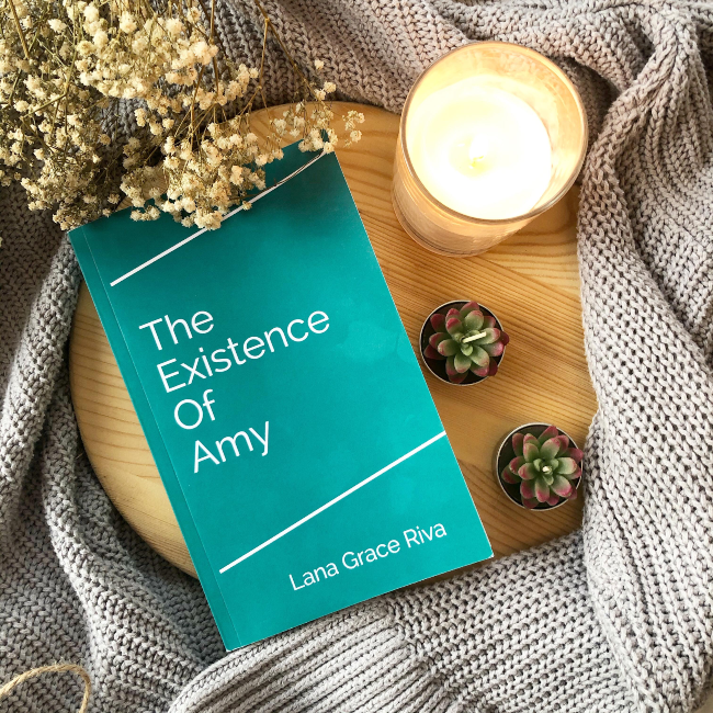A plain teal book cover for 'The Existence of Amy' on a brown chopping board on top of a grey cardigan, with baby's breath flowers