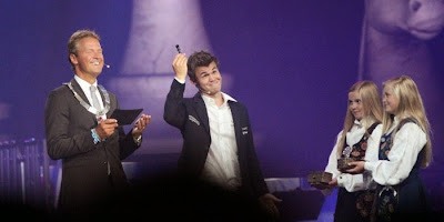 Le champion du monde d'échecs Magnus Carlsen montre le roi noir - Photo © site officiel