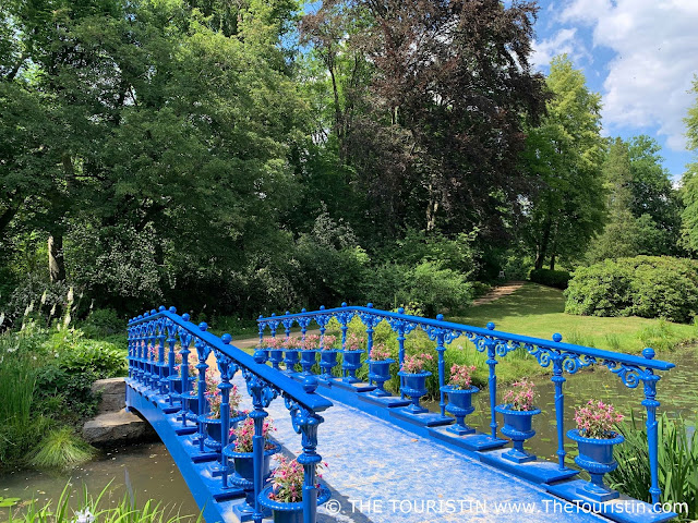 A bright- to dark blue painted iron bridge decorated with pink fuchsias over a pond, which leads to a sand paved path that lays under large trees.