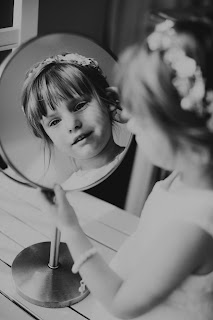 Professional photos of flower girl looking into the mirror.