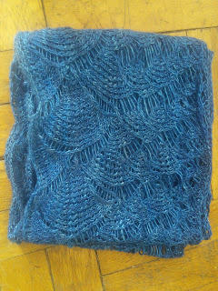 a lace scarf folded up on itself, knit in dark blue yarn. The lace is a shell motif, progressing into smalls and finally into a mesh.