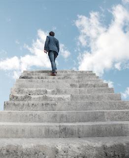 profissional de terno no topo da escada perto do céu