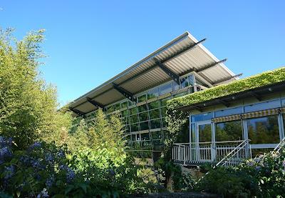Sportbad Heidberg. Glasfront des Sportbad-Teils mit emporstrebendem Dach.