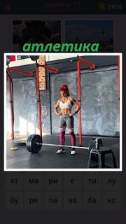 женщина занимается тяжелой атлетикой, в зале со штангой