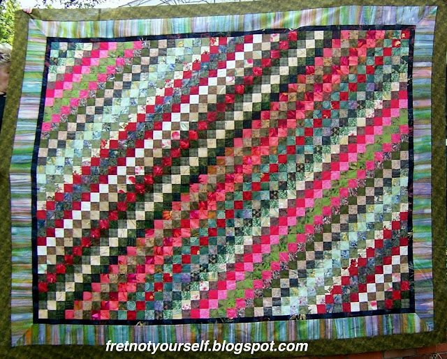 Postage Stamp quilt in greens, reds, pinks and cream