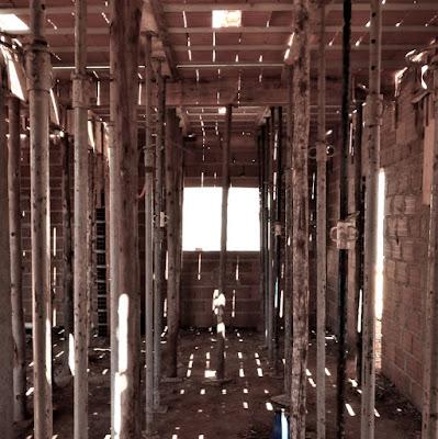 Obra no sistema tradicional, em fase de montagem da laje piso, com linhas de escoramentos para sustentar previamente os painéis pré-moldados, intercalados com lajotas cerâmicas.