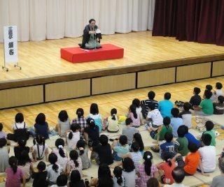 親子で楽しむ三遊亭楽春の学校で落語鑑賞会の風景。