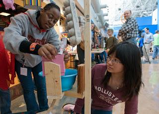 Two youth working on Rube Goldberg machine