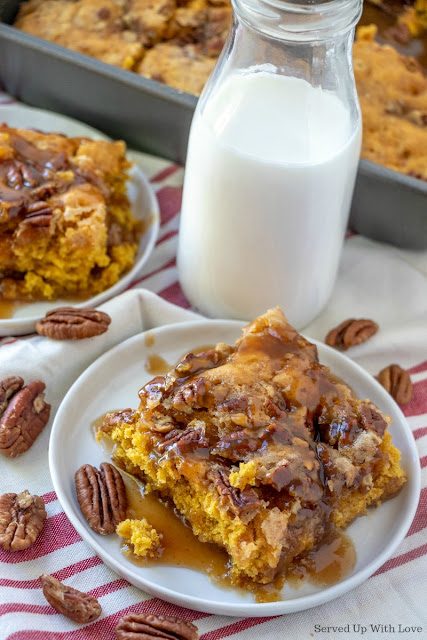 Pumpkin cobbler topped with pecan, sauce, served on white plate with a glass of milk
