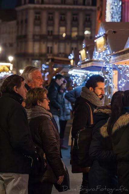 Personas mirando un puesto del mercadillo navideño