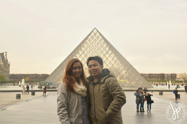 man and woman photo with glass pyramid in the background
