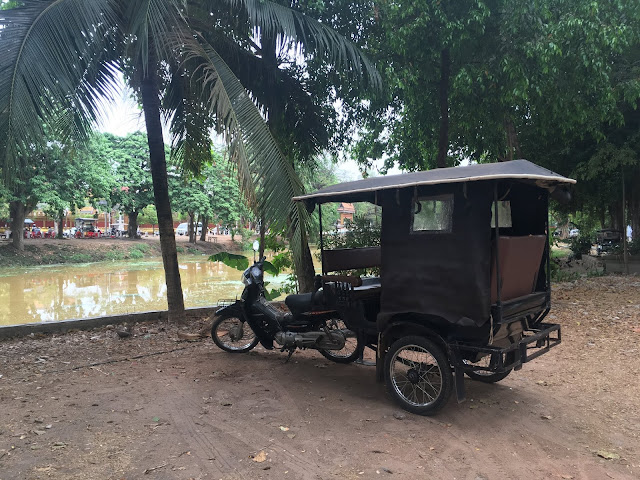 a tuk-tuk parked along the river in Siem Reap, Cambodia