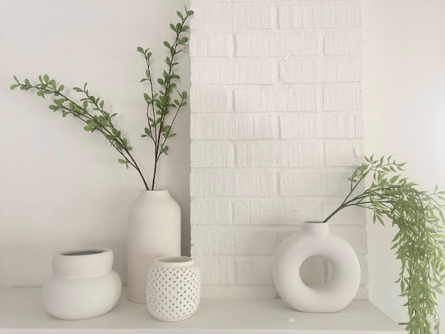 collection of modern white sculptural vases on fireplace mantle