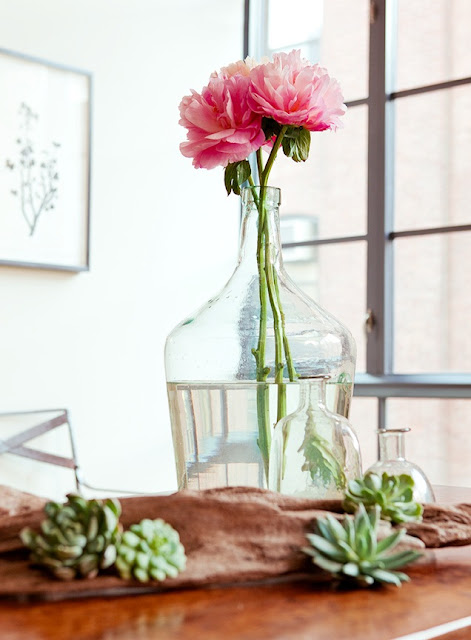 Close up of dining room centerpiece with pink flower, succulents, and reclaimed wood table