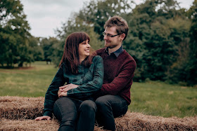 Laura and her partner Ben, sitting on hay