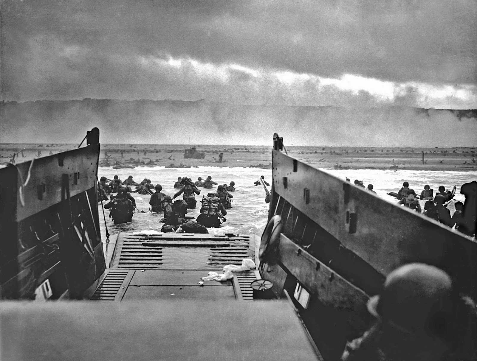 many soldiers running out of landing craft onto the beaches of normandy to illustrate blog post about anniversary of d-day