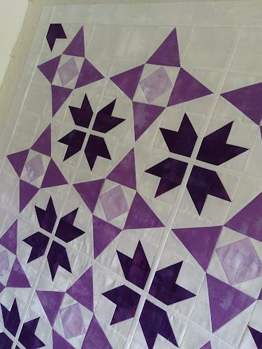 Partial quilt top with stars in 3 shades of purple