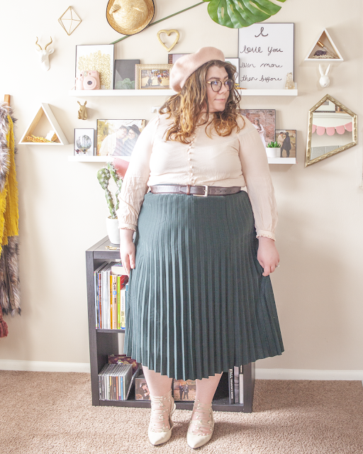 An outfit consisting of a pastel pink beret, pastel pink Peter Pan collar blouse tucked into a green pleated skirt with sheer pastel floral embroidered socks and beige slingback heels.
