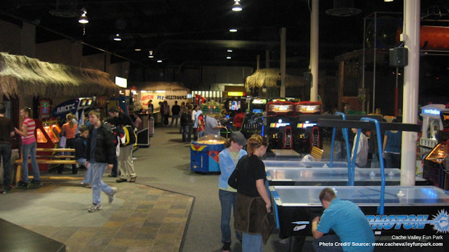visitors playing arcade games and air hockey