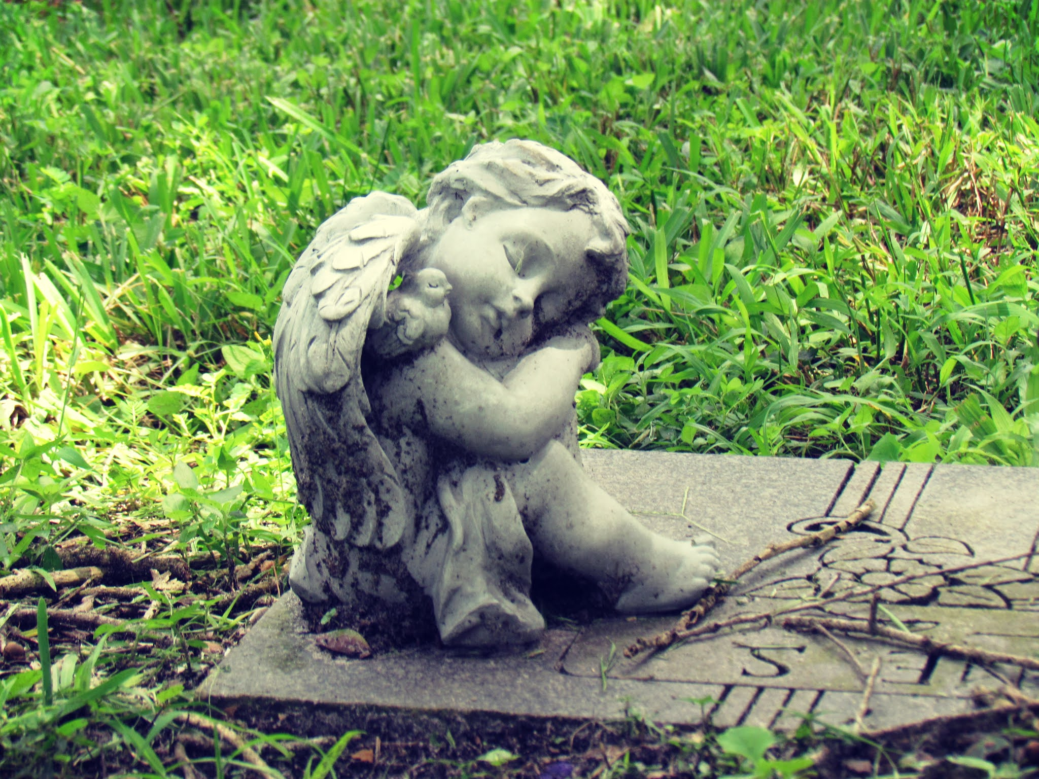 A headstone with an angel statue in the garden of the Dunedin Cemetery in Florida