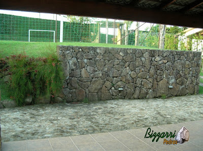 Muro de pedra com pedra bruta com o piso de pedra e o detalhe no canto do muro de pedra o muro de pedras soltas sem cimento com nichos na pedra para execução do paisagismo e o piso de pedra com pedra bruta.