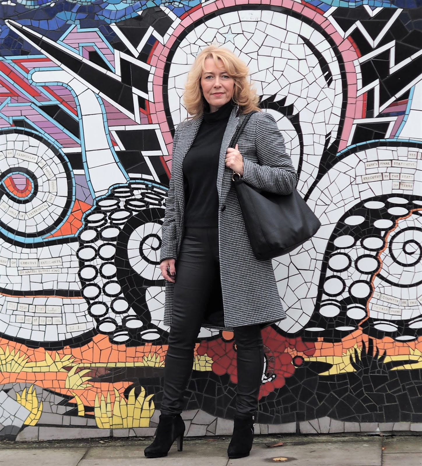 Image showing a 50 plus woman next to a colourful mural wearing black leggings black ankle boots and a tweed coat