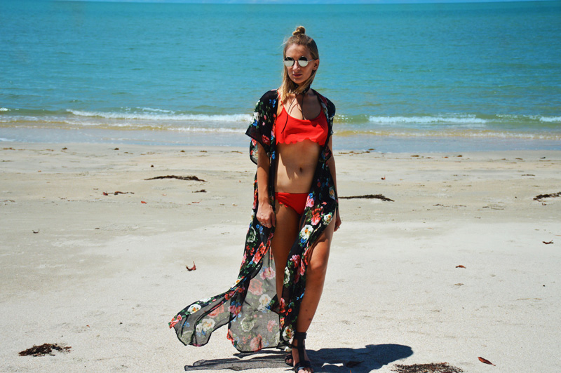 tanned blonde girl wearing scallop edge red bikini and rose print floral maxi kimono