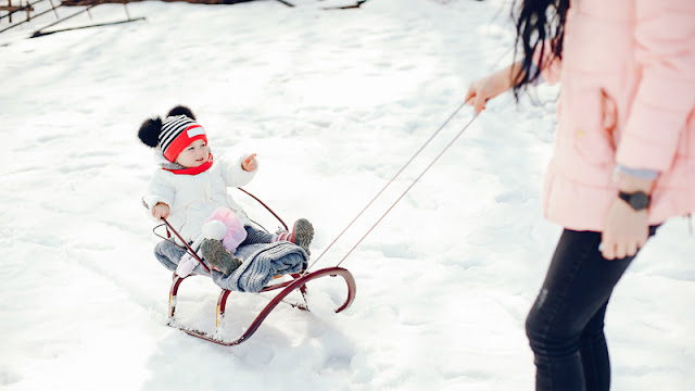 a mother pulling a small child through the snow on a sled