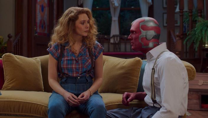 Imagem: Wanda sentada no sofá com Visão, agachado ao lado dela, em sua forma andróide com a pele metálica vermelha e verde, ambos se encarando como se estivessem discutindo.