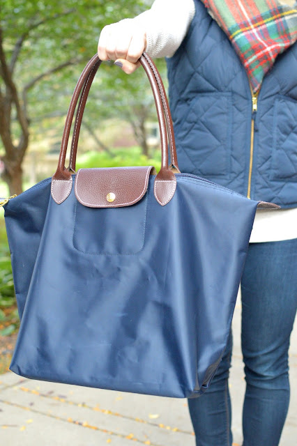 navy longchamp purse with a navy puffer vest
