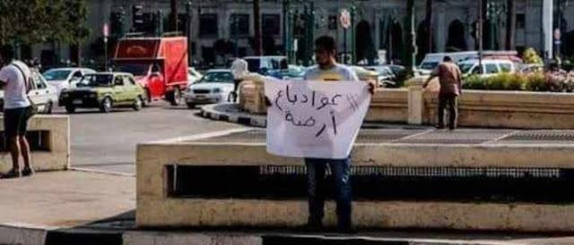 """شاب يرفع لافتة في التحرير """"عواد باع ارضه"""" تعرف ماذا حدث له ؟"""