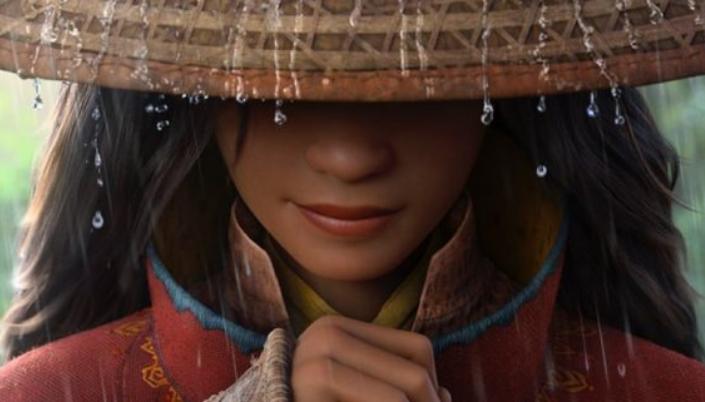 Imagem: a personagem Raya, uma jovem asiática com cabelos compridos, um chapéu de palha que esconde a parte de cima do seu rosto e a protege das gotas de chuva que caem ao seu redor, um sorriso e as mãos envoltas no cabo de uma espada e os trajes vermelhos com detalhes dourados com traços do Leste Asiático.