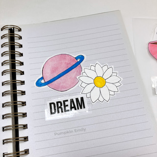A planet, flower and dream stickers in a journal.