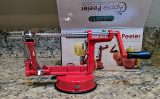 The red enameled Spiralizer has a long bright steel screw to push the apples through the peeling and slicing mechanism. The cardboard box is in the background.