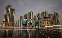 1Workers from Wuhan Guangsheng Photovoltaic installed solar panels on the roof of a building in Wuhan, China, last month. China has become a defender of an ambitious climate change policy. (Credit: Kevin Frayer/Getty Images) Click to Enlarge.