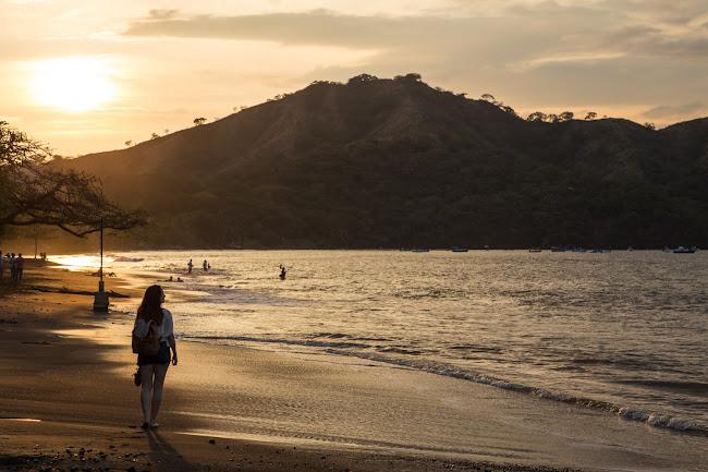 Lena paseando por la playa mientras el sol se pone