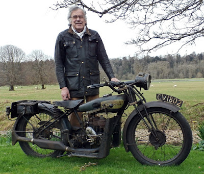 Man standing with vintage Royal Enfield motorcycle.