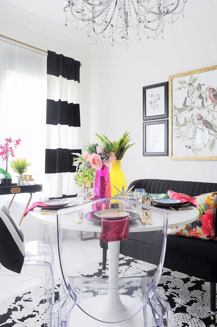 An eclectic and bold dining room with botanicals, florals, black and white accents and punches of pink and yellow. A stunning small space.