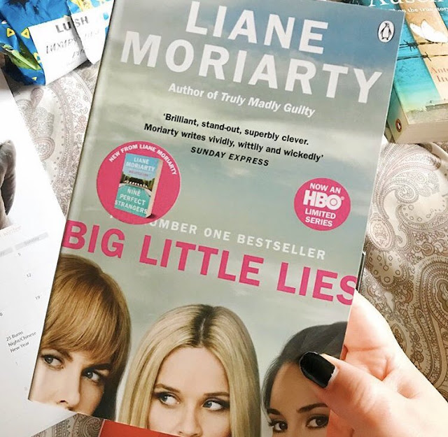 Big Little Lies by Liane Moriarty book held up in front of pink bedding