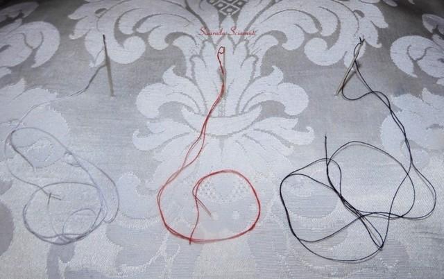 Cuscino con tre aghi appuntati con filo bianco, rosso e nero