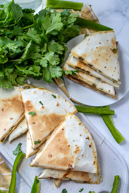 Philly Cheesesteak Quesadillas on a platter and plate with parsley garnish