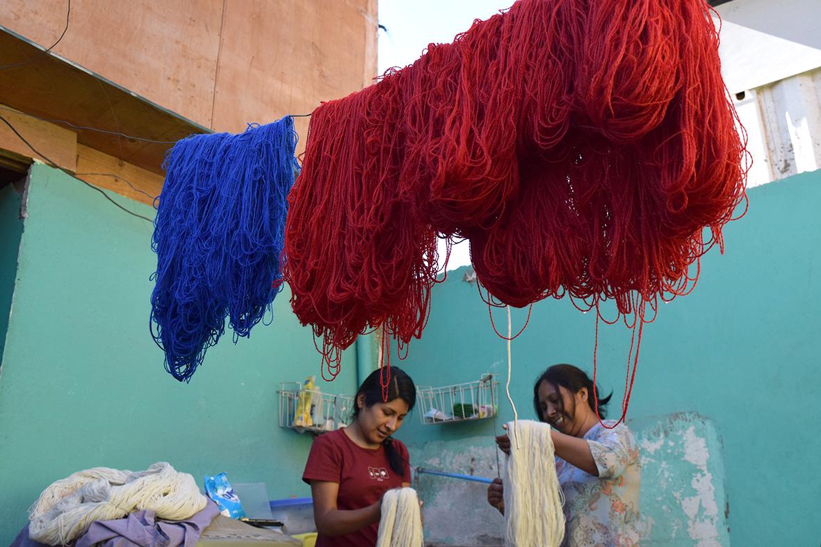 se ven colgadas lanas rojas y celestes secándose después de teñirse
