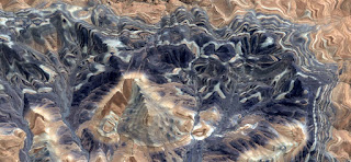 Stone texture African desert photographed from the air,mauve and dark blue with white parallel lines snaking between the rocks