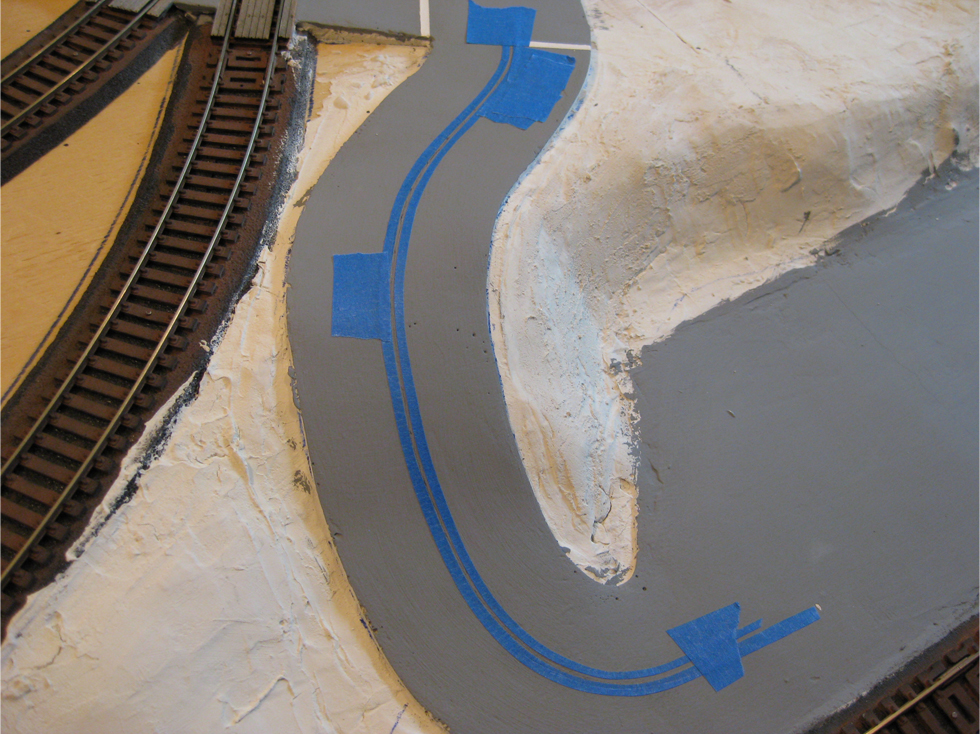 Center lines masked out with narrow blue masking tape on a plaster road