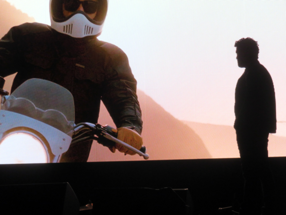 Man in front of movie screen showing motorcyclist.