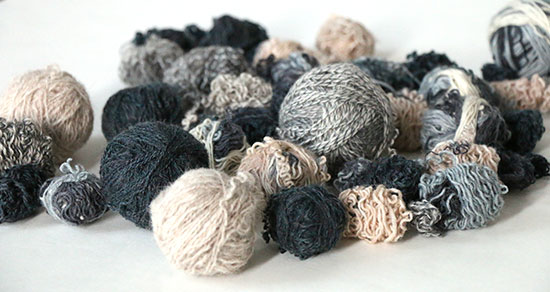 Small balls of unravelled sock yarn in shades of gray and beige on a white background.
